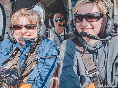 Three individuals on a helicopter tour. Deciding on an excursion requires researching different tour companies to see what each tour offers and at what price.